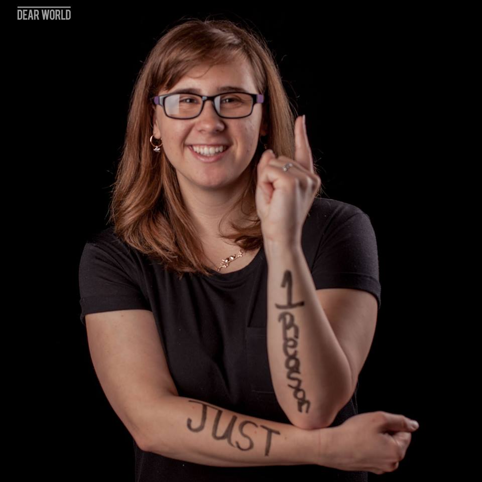 Cute girl with one reason written on arms